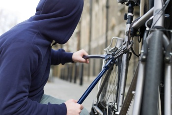 A thief stealing a bike --- Image by © Image Source/Corbis